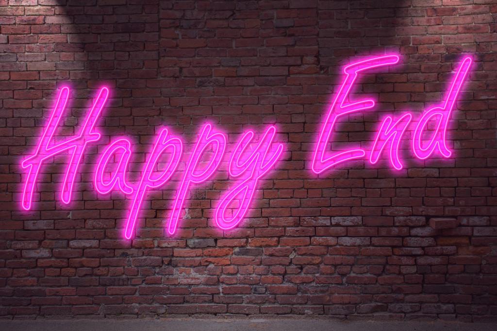 Leuchtreklame Happy End an Ziegelsteinmauer